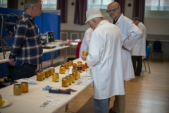 National Honey Judge Mike Duffin (centre) discusses entries with stewards Larry Phipps (L - Melksham BKA) and John Barber (R - Kennet BKA)  at the Wiltshire Bee & Honey Day 2019